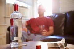 Homem que senta-se em Sofa With Bottle Of Vodka e em cigarros foto de stock