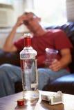 Homem que senta-se em Sofa With Bottle Of Vodka e em cigarros fotografia de stock