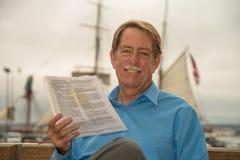 Homem que senta-se em um banco com documentos judiciais em seu hadn Fotos de Stock Royalty Free