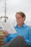 Homem que senta-se em um banco com documentos judiciais em seu hadn Imagem de Stock Royalty Free
