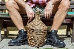 Homem que senta-se em um banco com garrafão Imagem de Stock Royalty Free