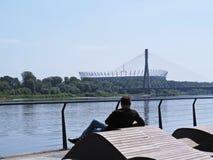 Homem que senta-se em um banco de rio do bulevar e que aprecia a vista bonita no estádio de futebol nacional imagens de stock royalty free