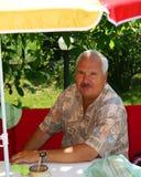 Homem que senta-se em um banco do piquenique. ilustração do vetor