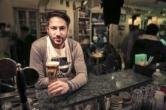 Homem que senta-se em um bar Fotografia de Stock Royalty Free