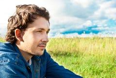 Homem que senta-se em um campo Imagem de Stock
