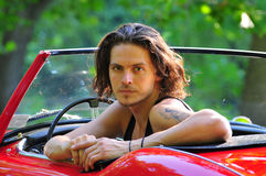 Homem que senta-se em um carro vermelho Foto de Stock
