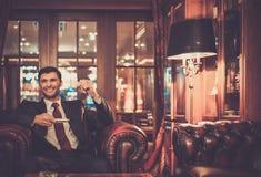 Homem que senta-se em um interior do luxo Foto de Stock Royalty Free