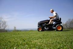 Homem que senta-se em um lawnmower Fotos de Stock