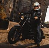 Homem que senta-se em uma motocicleta do café-piloto imagem de stock royalty free