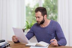Homem que senta-se fazendo o documento em um escritório domiciliário Imagem de Stock Royalty Free