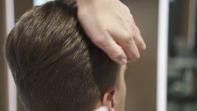 Homem que senta-se na cadeira do conforto da barbearia no cabelo que corta o proc video estoque