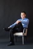 Homem que senta-se na cadeira no fundo escuro successful fotografia de stock