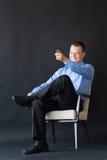 Homem que senta-se na cadeira no fundo escuro successful imagem de stock