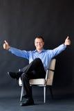 Homem que senta-se na cadeira no fundo escuro successful imagem de stock royalty free