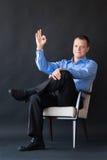 Homem que senta-se na cadeira no fundo escuro successful fotos de stock