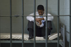 Homem que senta-se na cama na cela Imagem de Stock Royalty Free