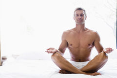 Homem que senta-se na cama que faz a ioga Fotos de Stock Royalty Free