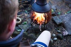 Homem que senta-se na frente do fogo Abra a chama com conceito do BBQ com fogueira fogueira no crepúsculo com o campista na frent fotos de stock royalty free