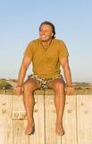 Homem que senta-se na luz do sol. fotografia de stock royalty free