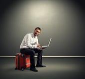 Homem que senta-se na mala de viagem Imagem de Stock