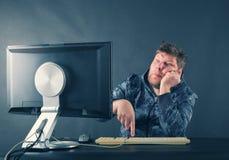 Homem que senta-se na mesa que olha no tela de computador fotos de stock