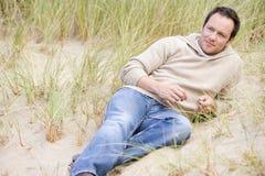 Homem que senta-se na praia Fotografia de Stock Royalty Free