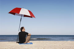 Homem que senta-se na praia foto de stock royalty free