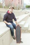 Homem que senta-se na rua com skate. foto de stock