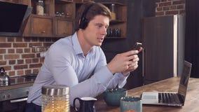 Homem que senta-se na tabela com bacia e portátil video estoque