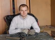 Homem que senta-se na tabela com broca Imagem de Stock Royalty Free