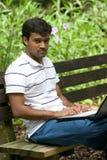 Homem que senta-se no banco Fotografia de Stock Royalty Free
