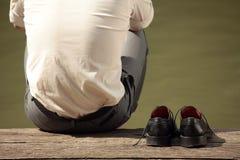 Homem que senta-se no cais Imagens de Stock