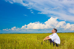 Homem que senta-se no campo Fotografia de Stock