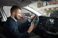 Homem que senta-se no carro que guarda as mãos no volante fotos de stock