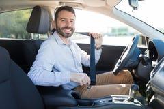 Homem que senta-se no cinto de segurança da asseguração do banco de carro fotos de stock royalty free