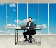 Homem que senta-se no escritório claro Fotos de Stock Royalty Free