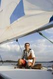 Homem que senta-se no Sailboat no lago - vertical fotografia de stock royalty free