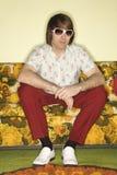 Homem que senta-se no sofá. foto de stock