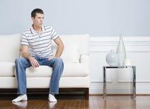 Homem que senta-se no sofá da sala de visitas imagem de stock