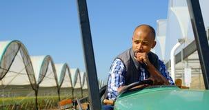 Homem que senta-se no trator na exploração agrícola 4k do mirtilo vídeos de arquivo