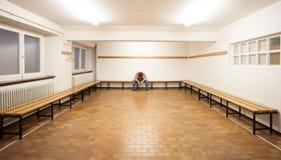Homem que senta-se no vestuário vazio Imagens de Stock