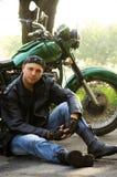 Homem que senta-se pela motocicleta Imagens de Stock
