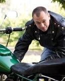 Homem que senta-se pela motocicleta Fotografia de Stock Royalty Free