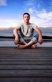Homem que senta-se perto da água na noite Imagens de Stock Royalty Free