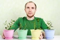 Homem que senta-se perto da tabela com plantas potted Imagem de Stock Royalty Free