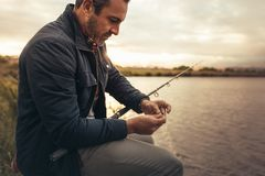 Homem que senta-se perto de um lago com vara de pesca foto de stock