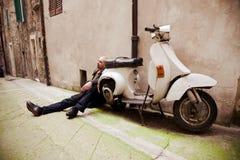 Homem que senta-se perto do 'trotinette' retro Imagens de Stock Royalty Free
