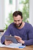 Homem que senta-se usando uma tabuleta em casa Imagem de Stock Royalty Free