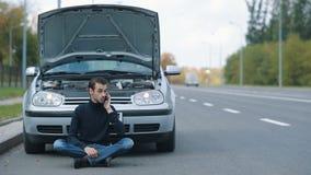Homem que siitting na estrada com quebrado vídeos de arquivo