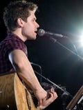 Homem que siniging e que joga a guitarra acústica Fotografia de Stock